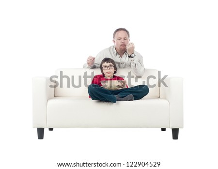 Father and son on living room sofa watching television while eating popcorn