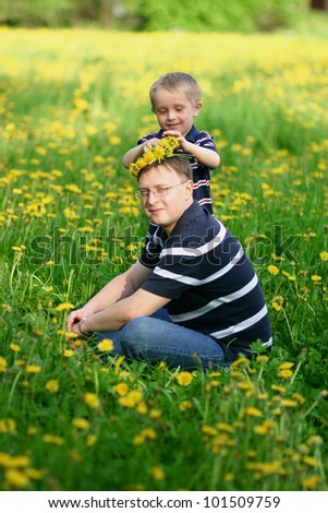 Father and son on same striped T-shirts outdoors - stock photo