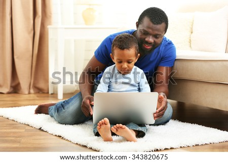 Father and son on sofa in the room - stock photo