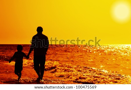 Father and son on the beach - stock photo