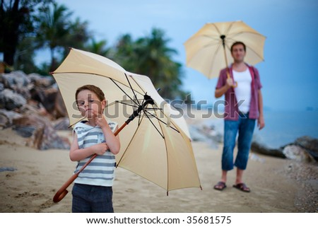Father and son on the beach at rainy evening