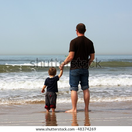 Father and son on the beach. They stand in the water and watch the sea. - stock photo