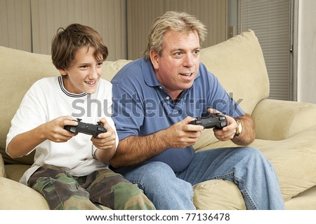 Father and son or uncle and nephew, playing video games at home. - stock photo
