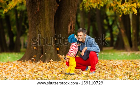 Father and son outdoors, kissing, dressed in colorful clothes. Autumn. - stock photo