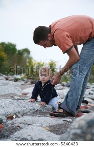 Father and son outside learning to crawl and walk - stock photo