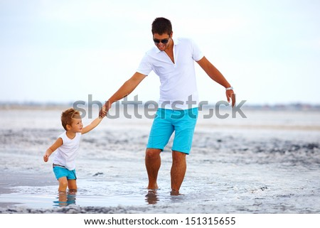 father and son overcome obstacles together, salted firth - stock photo