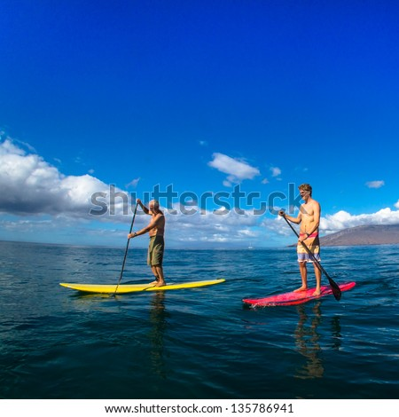 Father and son paddle boarding and exercising together - stock photo