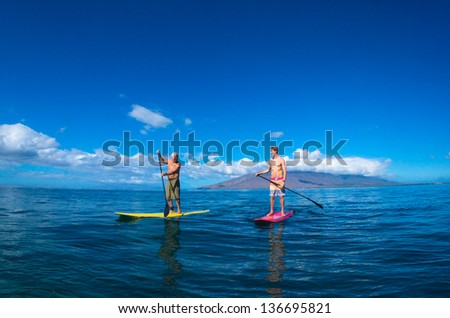 Father and son paddle boarding and exercising together