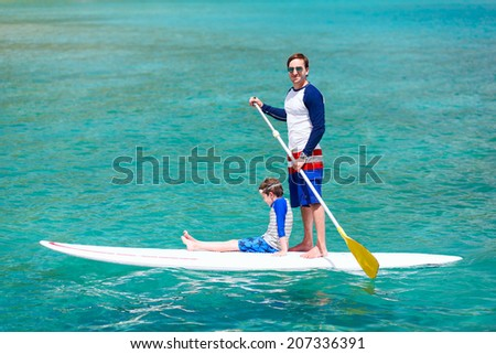 Father and son paddling on stand up board having fun during summer beach vacation - stock photo