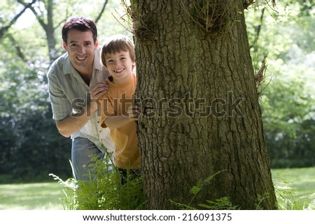 Father and son (8-10) peeking out from behind tree, smiling, portrait