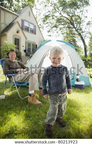 Father and son pitching a tent in the front yard - stock photo