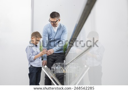 Father and son placing glass in dishwasher at kitchen - stock photo