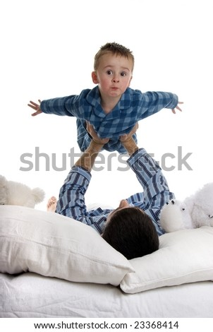 Father and son play in bed
