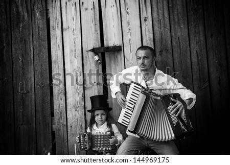 father and son playing accordion black and white - stock photo