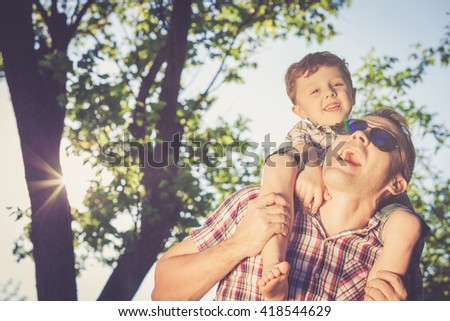 Father and son playing at the park at the day time. Concept of friendly family. - stock photo