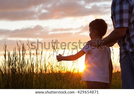 Father and son playing at the park at the sunset time. Concept of friendly family. - stock photo