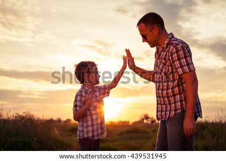 Father and son playing at the park at the sunset time. People having fun on the field. Concept of friendly family and of summer vacation. - stock photo