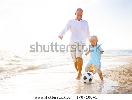 Father and Son Playing Ball on Beach - stock photo