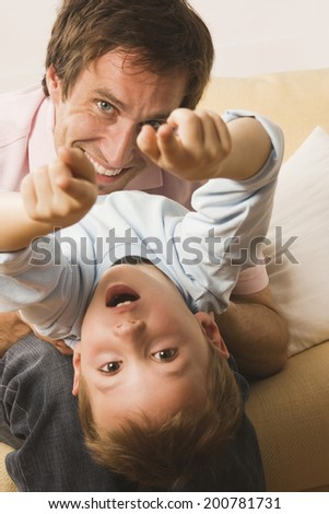 Father and son playing boy pointing with fingers close up
