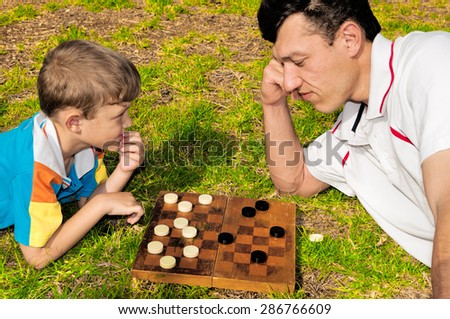 Father and son playing checkers on the grass in a city park - stock photo