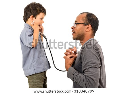Father and Son playing doctors with boy holding a stethoscope and listening to doctors heart as part of therapy. - stock photo
