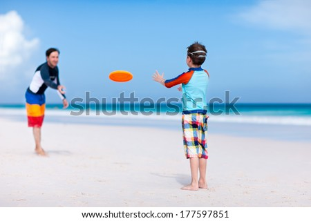 Father and son playing frisbee at beach - stock photo