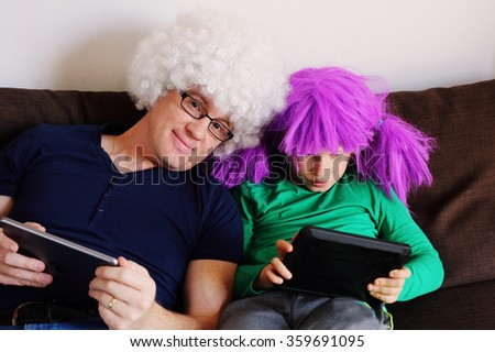father and son playing games on tablets - stock photo