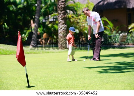 Father and son playing golf. Focus on flag. - stock photo