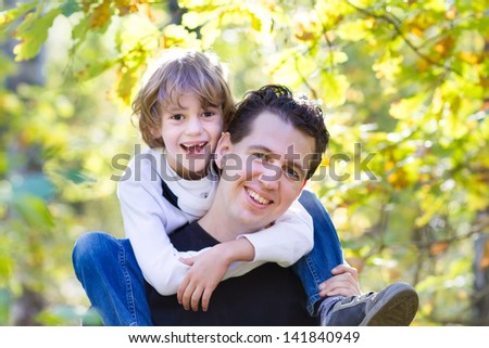 Father and son playing in a beautiful autumn park - stock photo
