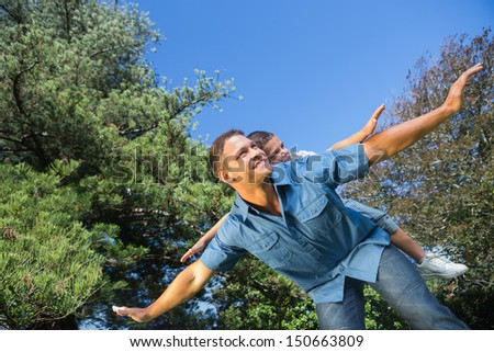 Father and son playing in a park on a beautiful summers day - stock photo