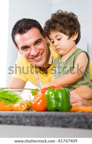father and son playing in modern kitchen - stock photo