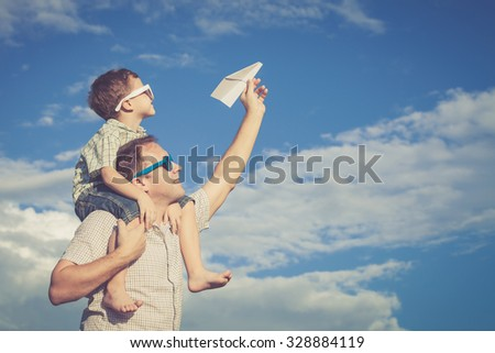 Father and son playing in the park  at the day time. Concept of friendly family. - stock photo