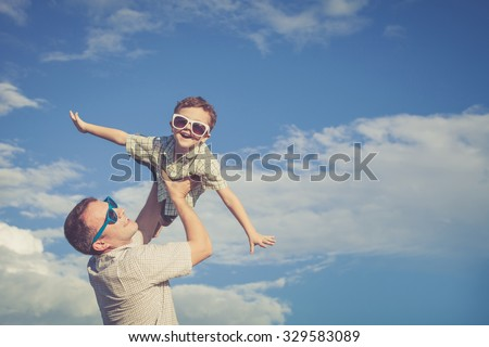Father and son playing in the park  at the day time. Concept of friendly family. Picture made on the background of blue sky. - stock photo