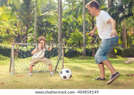 Father and son playing in the park  at the day time. Concept of friendly family. Picture made on the green meadow. - stock photo