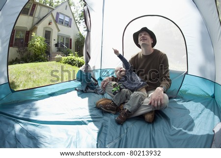 Father and son playing inside the tent in the front yard - stock photo