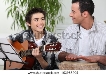 Father and son playing music - stock photo