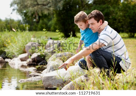 Father and son playing near park lake, looking for animals in the water - stock photo
