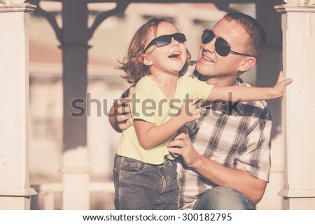 Father and son playing near the house at the day time. They sitting in the white gazebo. Concept of friendly family. - stock photo