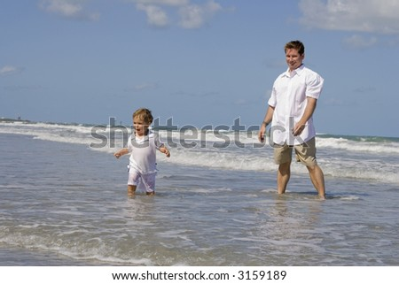 Father and son playing on a beach - stock photo