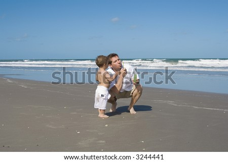 Father and son playing on a beach with bubbles. - stock photo