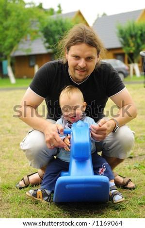 Father and son playing on a rocking-horse