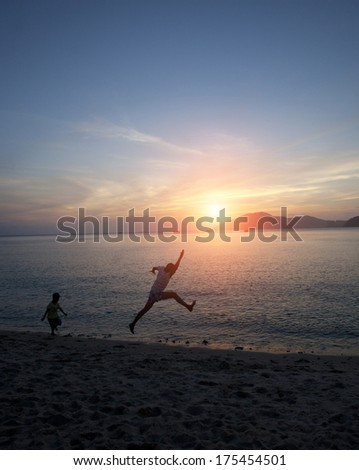 father and son playing on beach in sunset