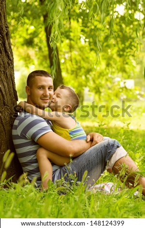 Father and son playing on green field
