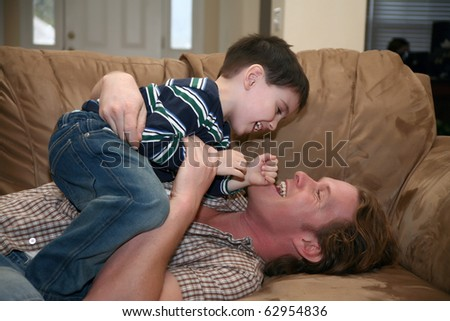 Father and son playing on sofa in home.