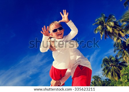 father and son playing on summer tropical beach - stock photo