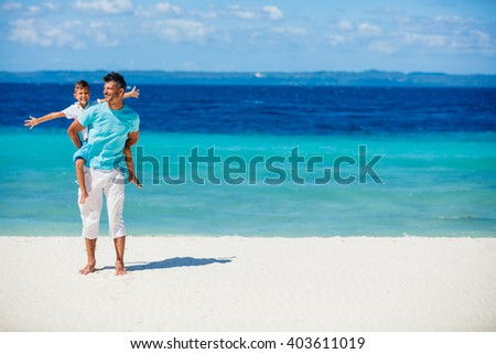 Father and son playing on the beach.