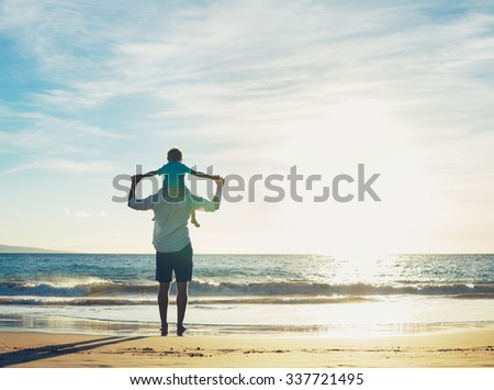 Father and Son Playing on the Beach at Sunset, Having Quality Family Time Together. - stock photo