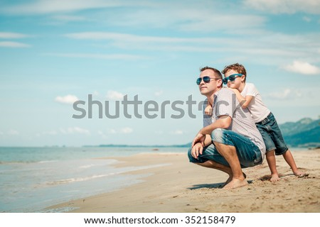 Father and son playing on the beach at the day time. Concept of friendly family.