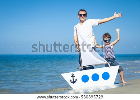 Father and son playing on the beach at the day time. Concept of happy friendly family.