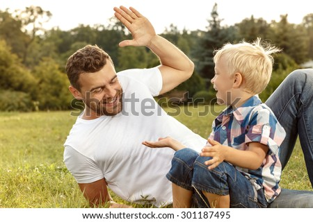 Father and son playing on the field - stock photo